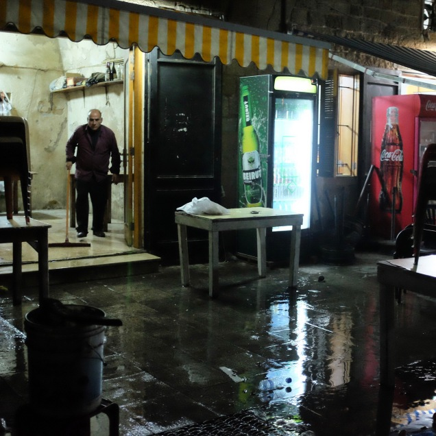 A man cleans his shop at midnight in the old port of Tyre.