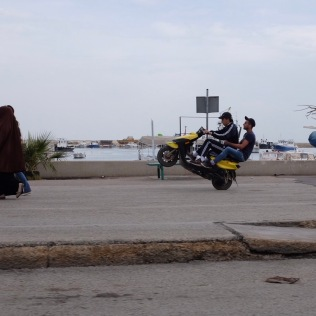 Teenagers attempt to get to 12 o'clock on the corniche in El Mina, an independent town within Tripoli.